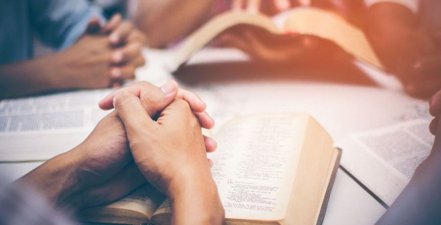 Hands clasped over Bible in prayer group