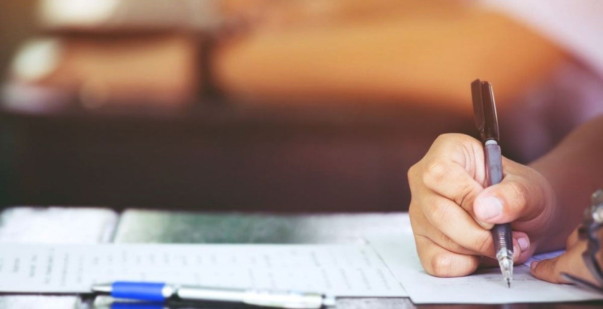 Close-up of hand holding a pen and writing an exam
