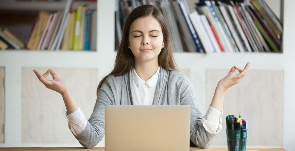 Woman in front of laptop meditating to calm anger