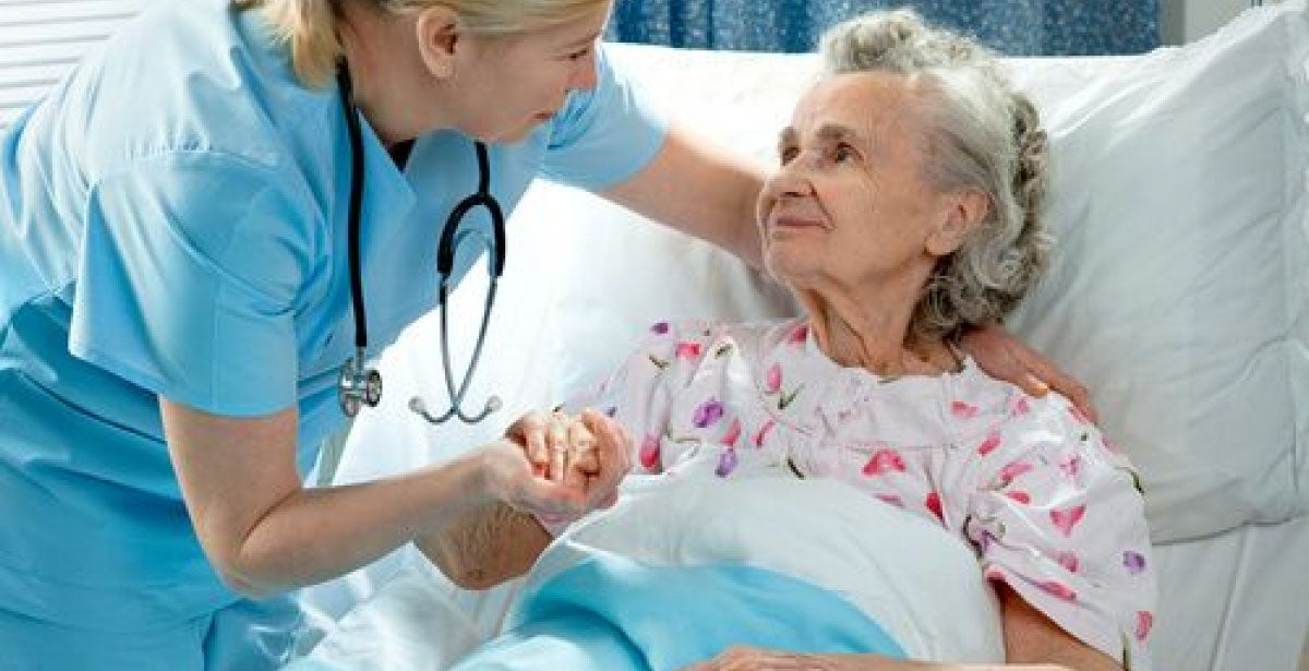 Nurse tending to elderly patient in hospital bed