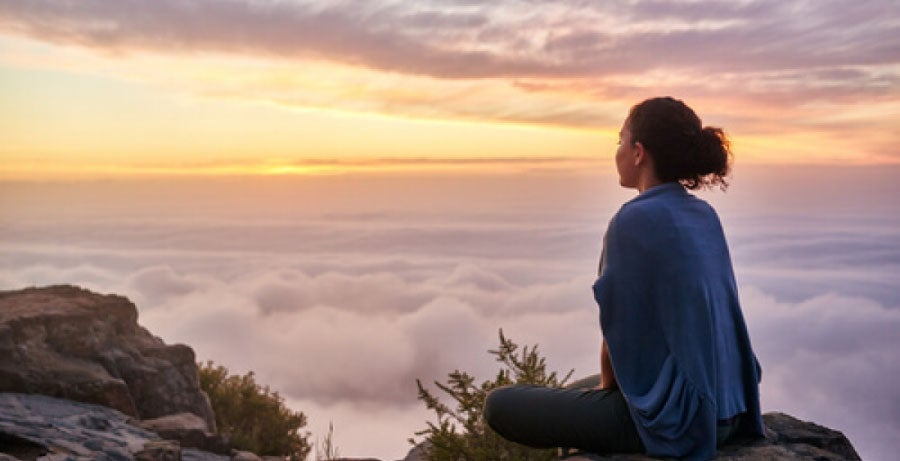 Woman on mountaintop looking out over clouds at sunrise