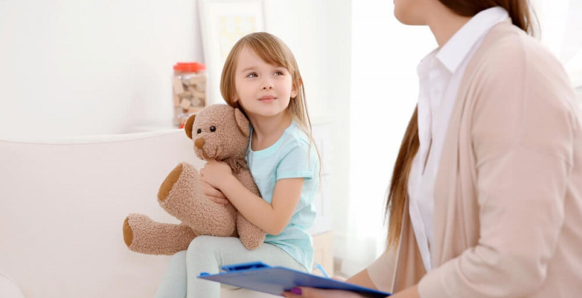 Social worker talking to vulnerable child with teddy bear