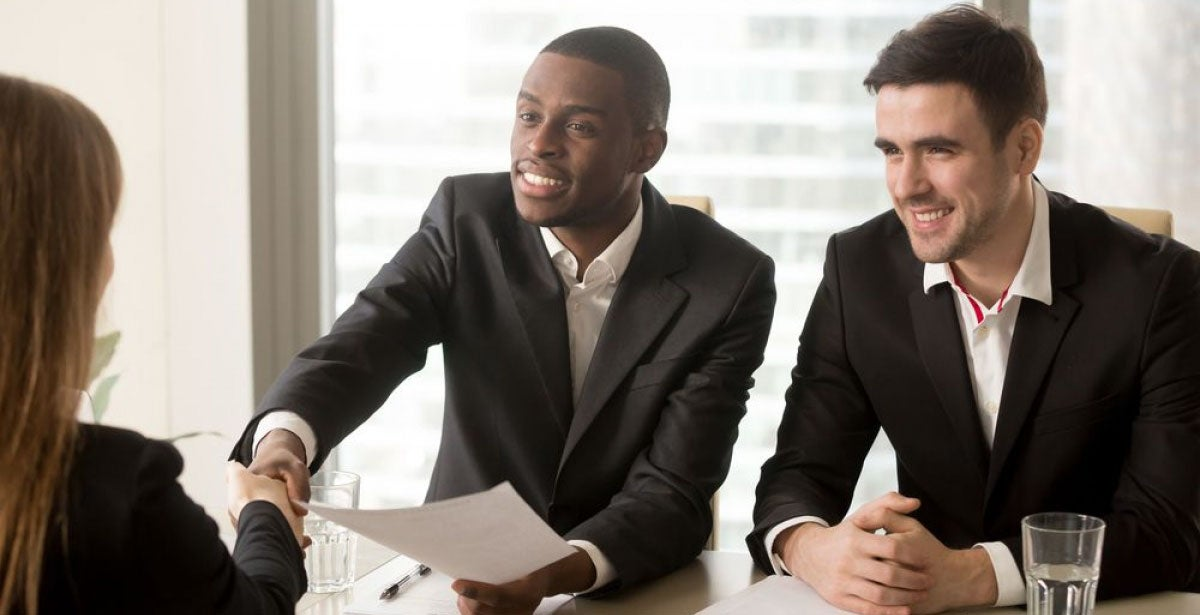 Two cheerful black and white recruiters welcoming female applicant on job interview