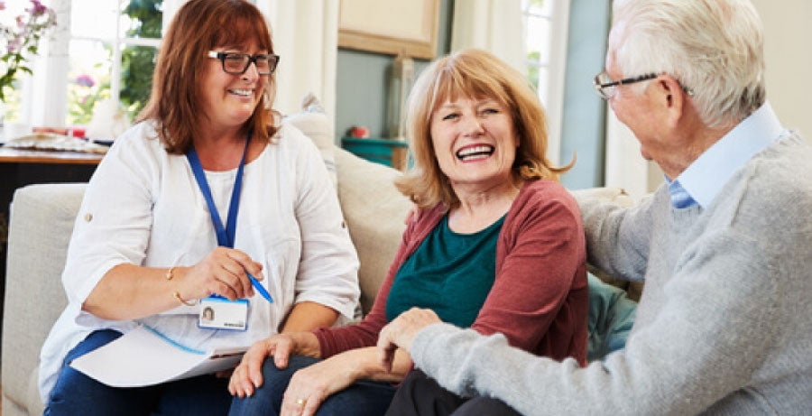 Social worker sitting on a sofa with elderly couple