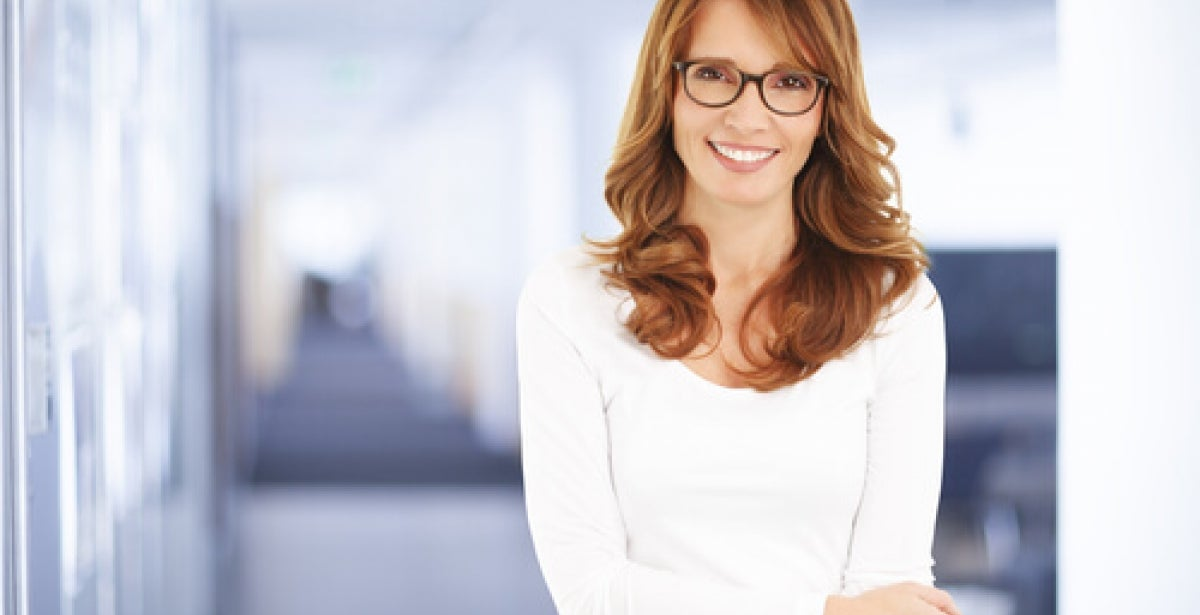 Woman in office wearing white top and smiling