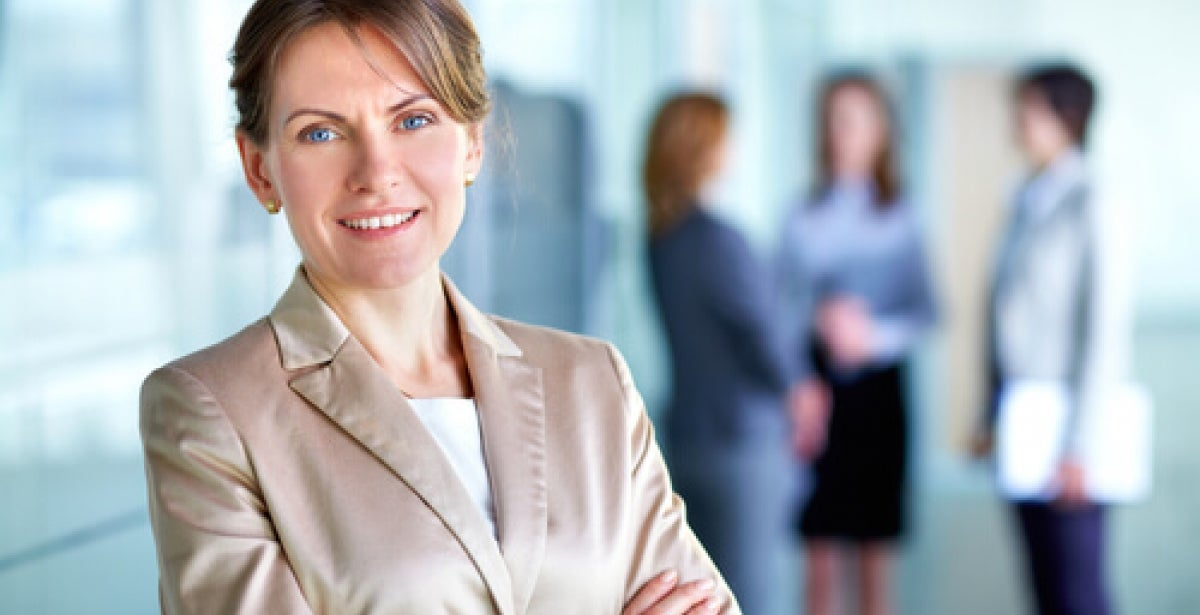Businesswoman with MBA in executive leadership crossing arms and looking accomplished