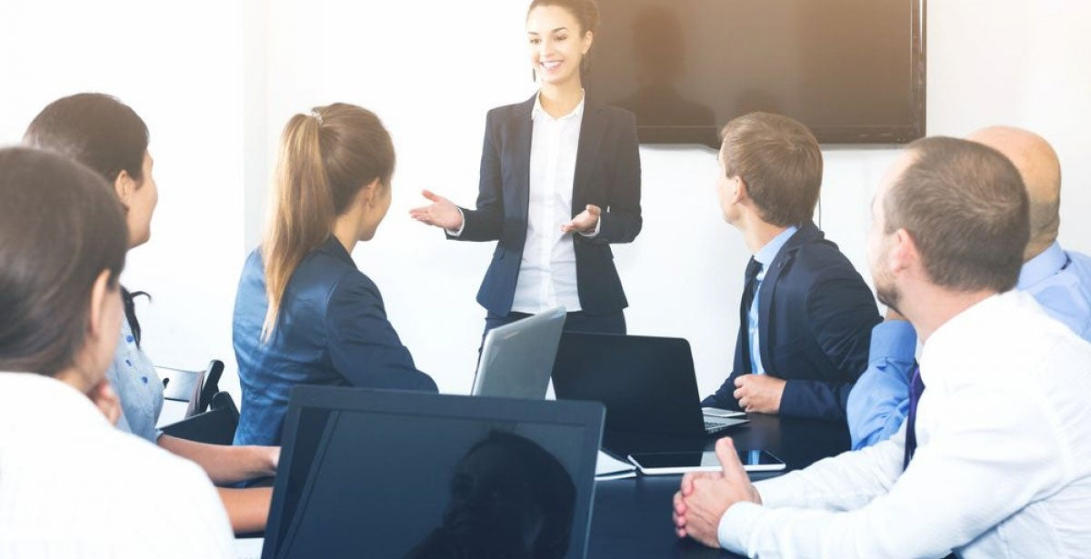 Young, smiling businesswoman leading a meeting in packed boardroom