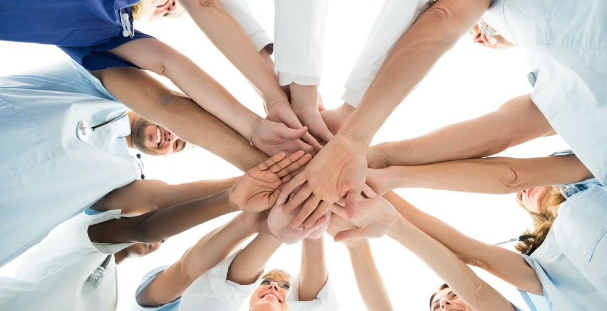 Group of nurses in a circle doing a team hand stack