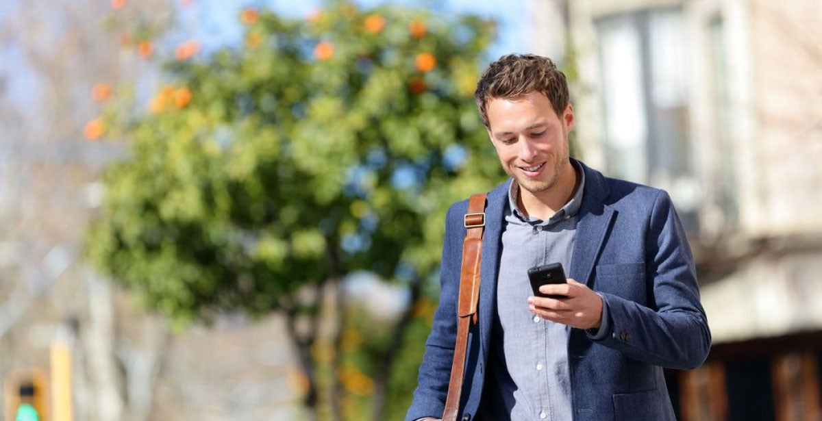 Well-dressed man smiling and looking at his phone while walking down the street