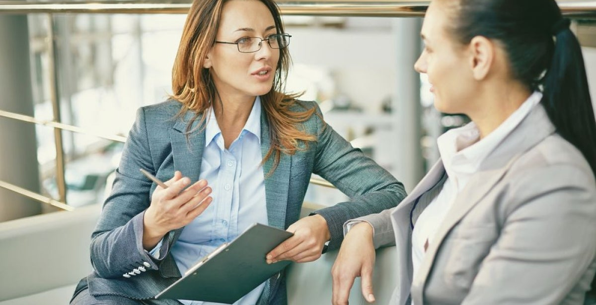 Businesswoman with clipboard explaining management concept to colleague