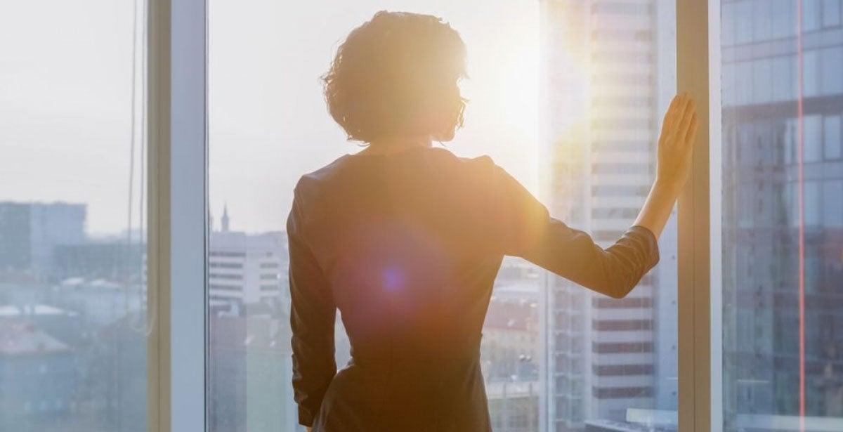Silhouette of businesswoman in sunlit office window