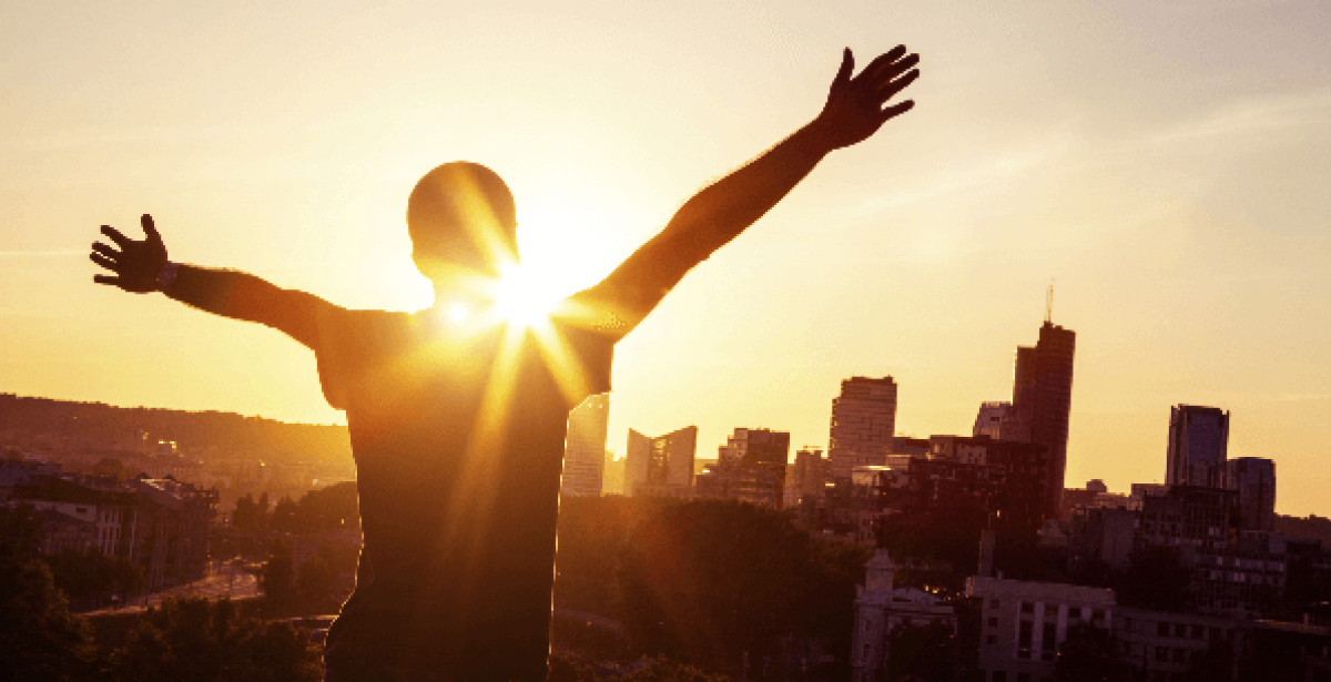 Man raising arms in praise while looking at city skyline at sunset