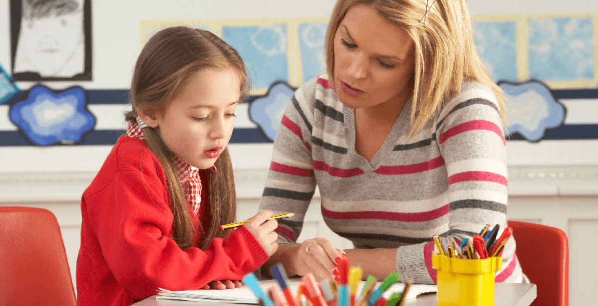 Kindergarten teacher working closely with young girl