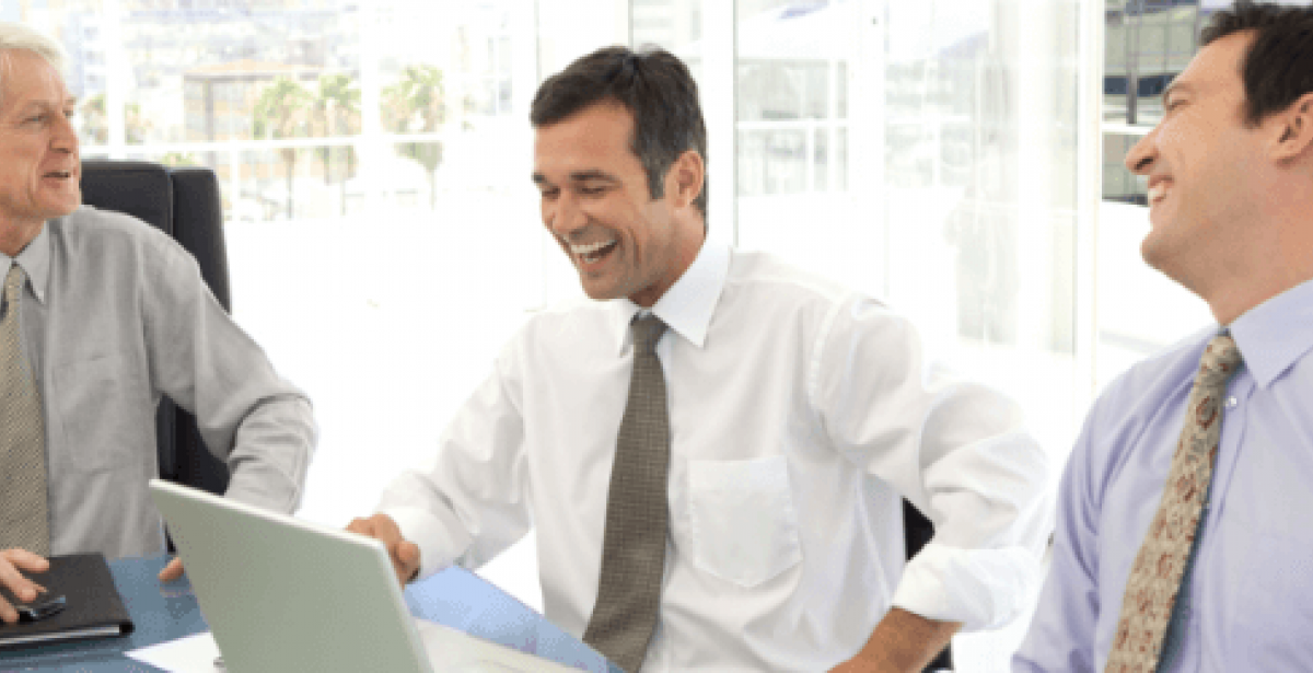 Businessmen laughing together in boardroom