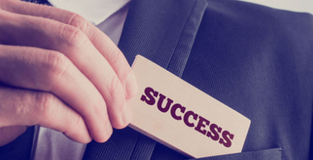 """Close-up of man in suit holding a piece of card with """"success"""" written on it"""