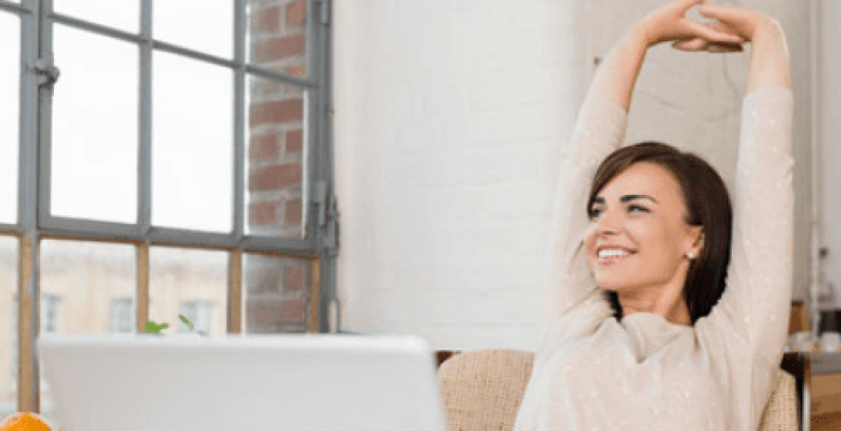 Woman stretching while working at home office