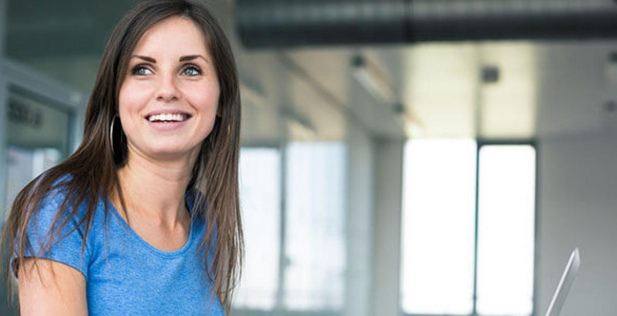 Female MBA grad smiling and looking off into the distance while working at computer