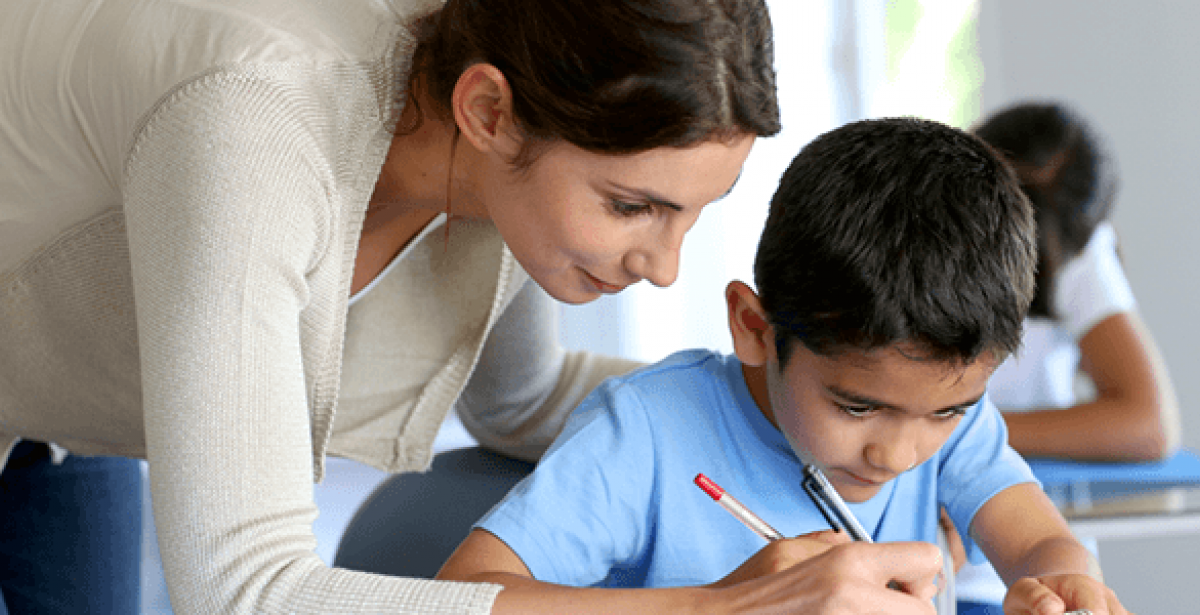 Teacher helping young ESL student