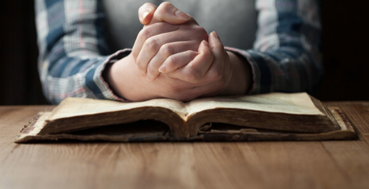 Clasped hands praying on top of old Bible