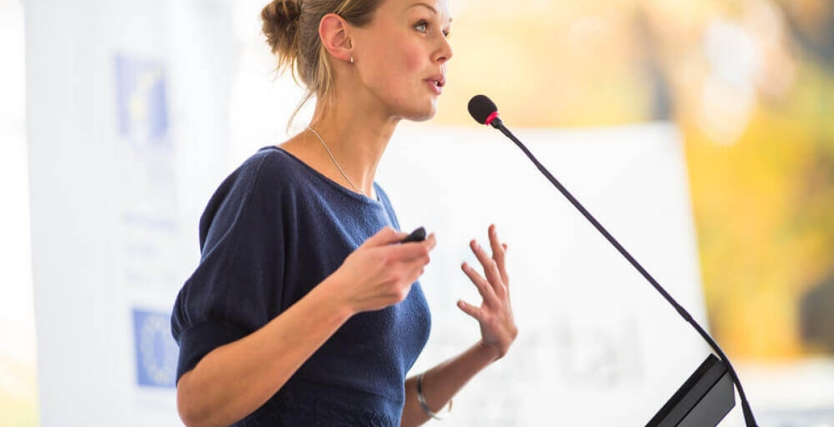 Woman delivering a presentation into microphone