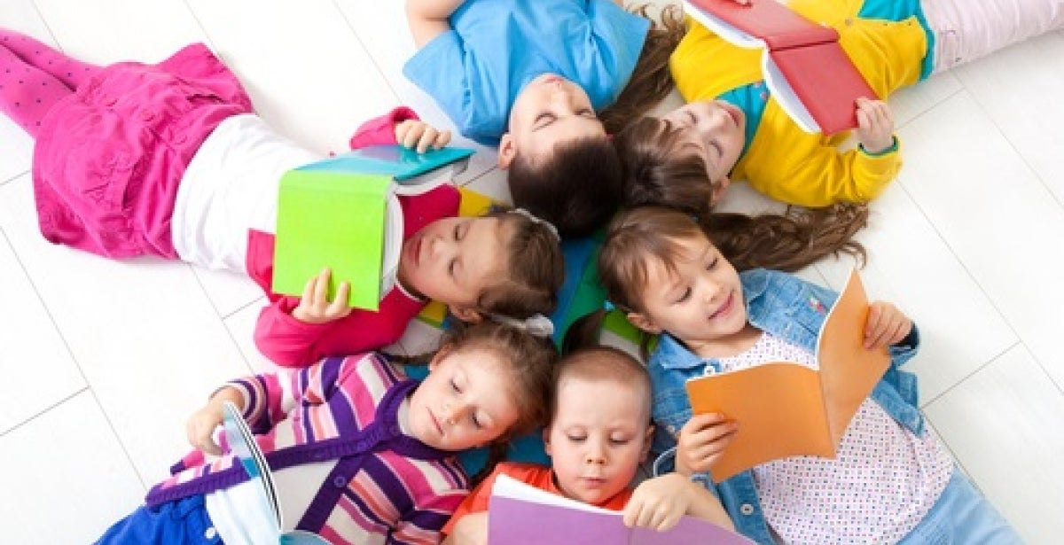 Children in bright colorful clothing lying down in a circle with their heads together