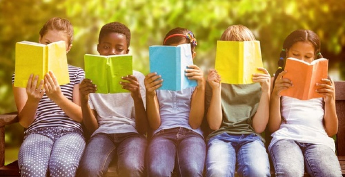 Group of young students reading colorful books outdoors