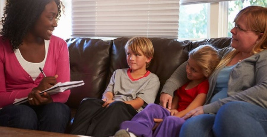Social worker talking to mother and two young children on leather sofa
