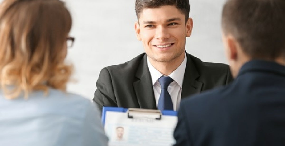 Man in suit talking to two employees about HR policies