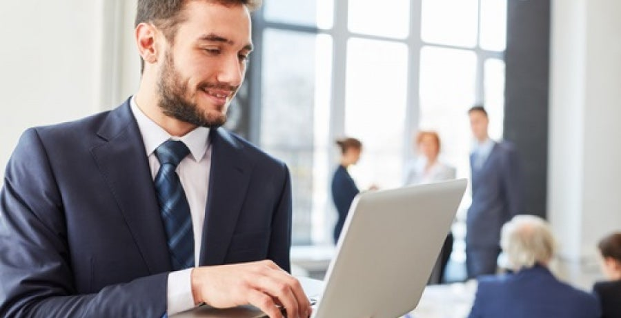 Man standing while typing on laptop in busy office