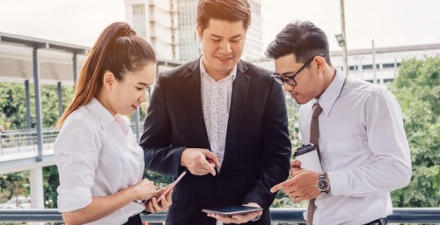 Businessman showing his two colleagues some information on a tablet device, outdoors