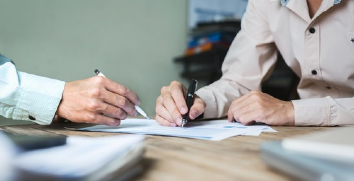 Close-up of two people signing a business contract