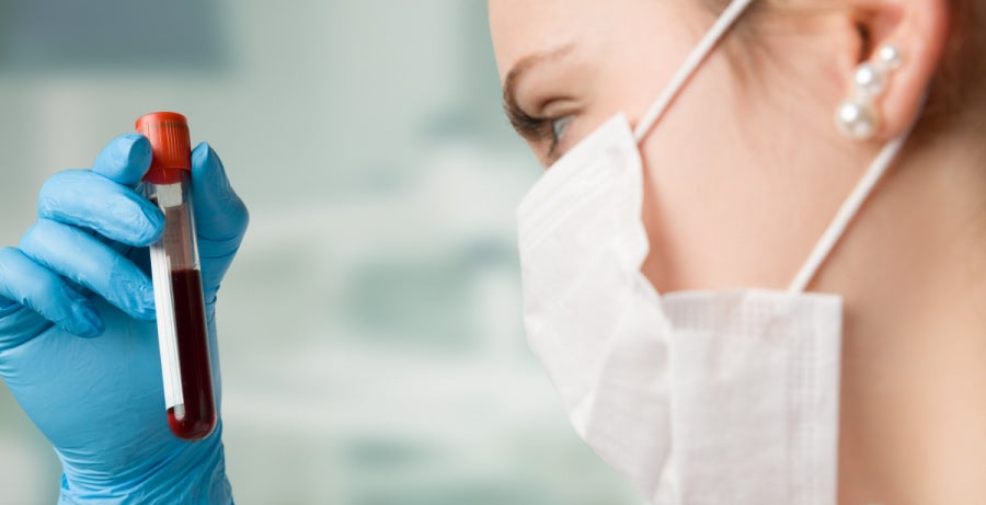 Nurse wearing face mask and rubber gloves, holding a vial of patient's blood