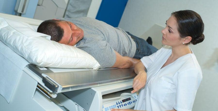 Nurse comforting man lying on hospital bed