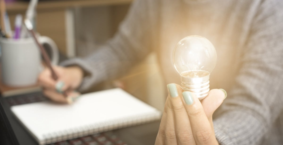 Woman working in front of laptop and holding up lightbulb