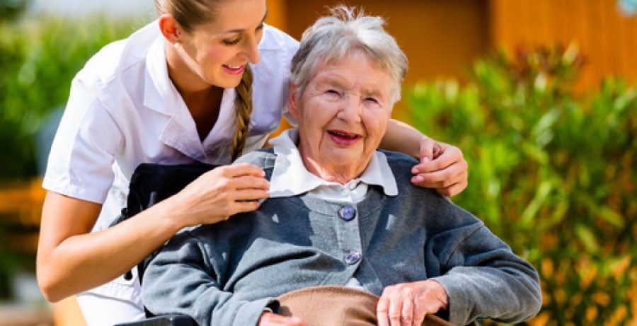 Adult-gerontology nurse practitioner interacting with an elderly patient in a wheelchair outdoors