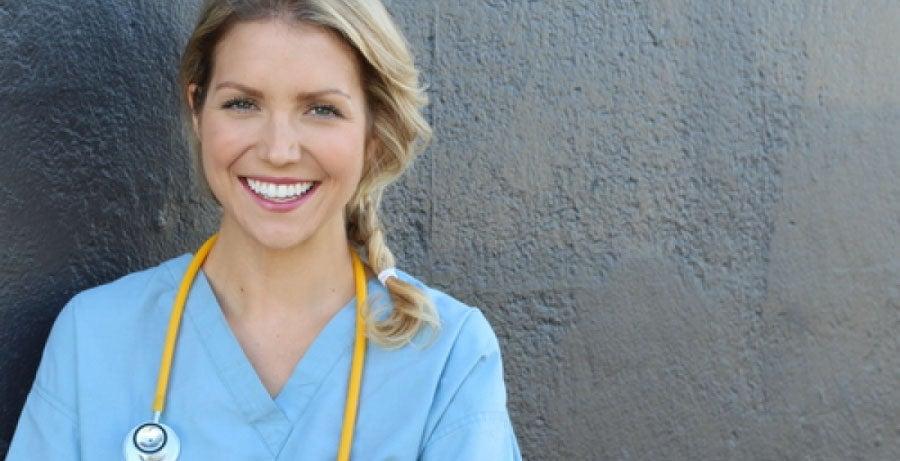 Registered nurse smiling against grey background