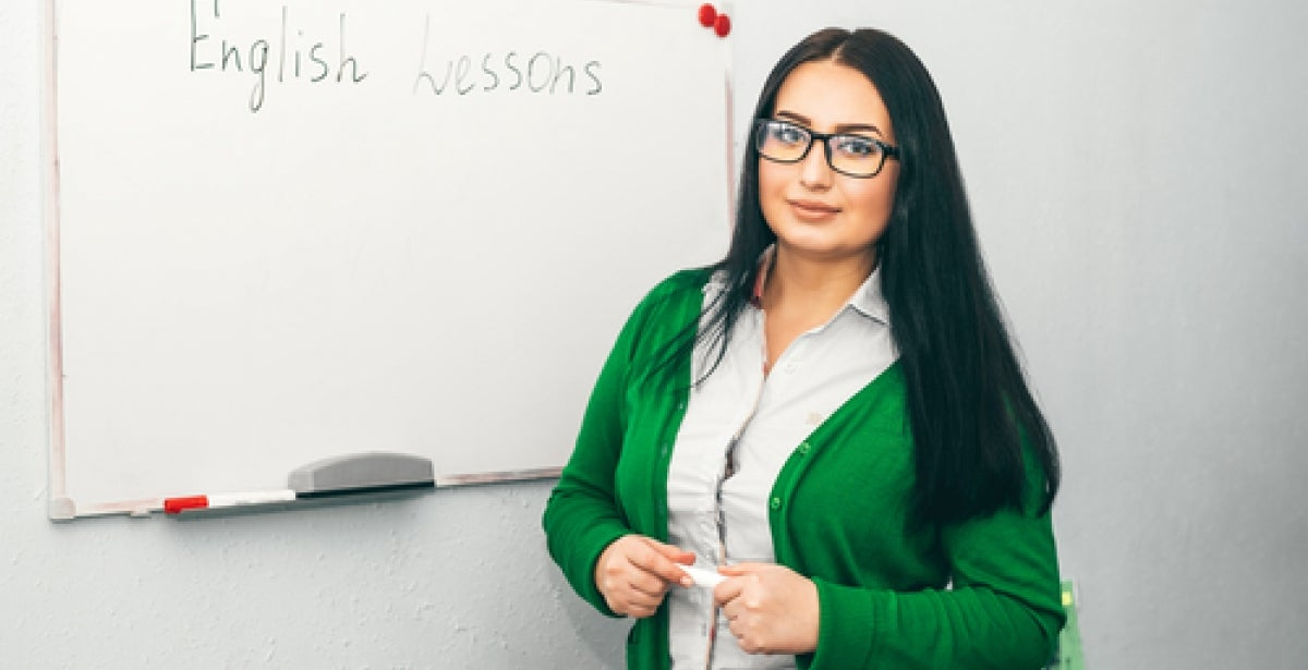 """TESOL instructor standing in front of whiteboard with """"English Lessons"""" written on it"""