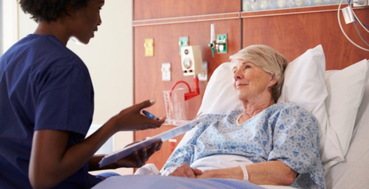 Bedside nurse tending to geriatric patient in hospital