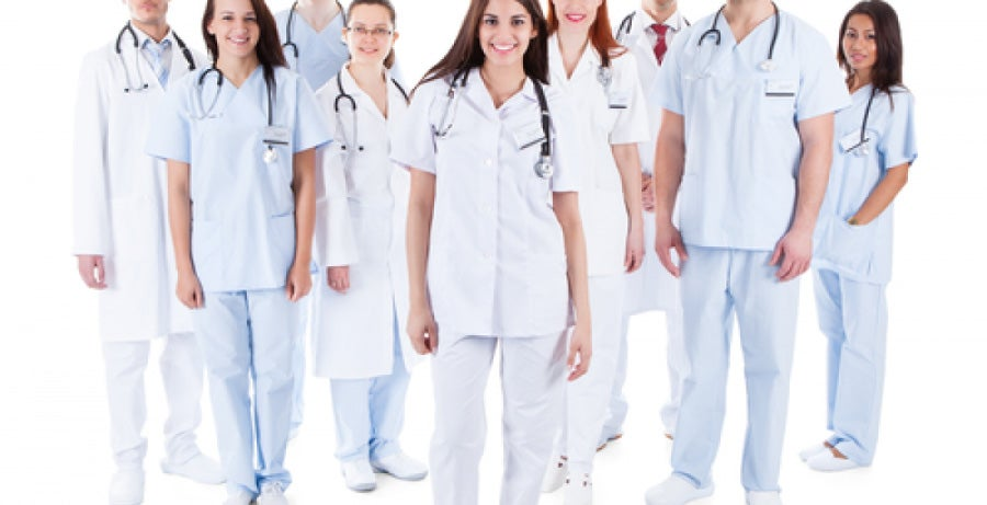 Group of nurses and doctors standing together against white background