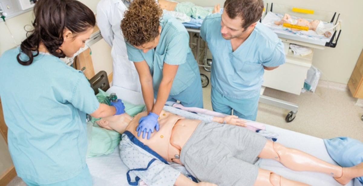 Nurses in hospital room doing training on a dummy