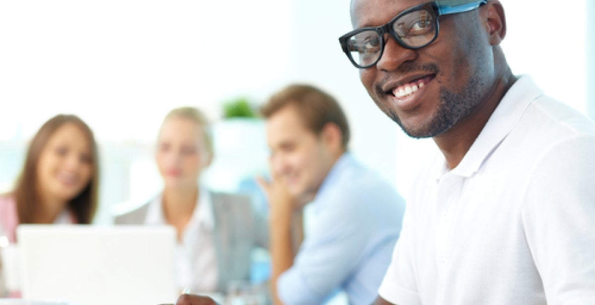 Man in glasses and white shirt smiling while participating in group project