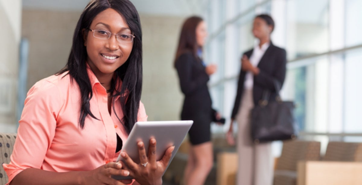 Online MBA student with tablet in office attire